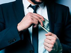 Homem colocando dinheiro no bolso interno do terno