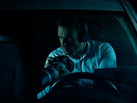 Homem dentro de um carro com uma camera na mão vigiando algo