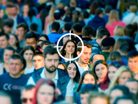 Uma multidão de pessoas e uma mira no centro da imagem focando em uma pessoa