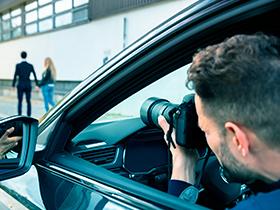 Homem dentro de um carro com uma camera na mão tirando foto de um casal